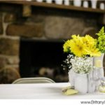 yellow and white flowers in white vases on a table