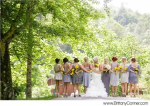 bridal party with their backs turned to the camera holding yellow and white flowers